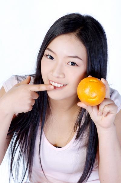 白い歯でオレンジをかじる女性